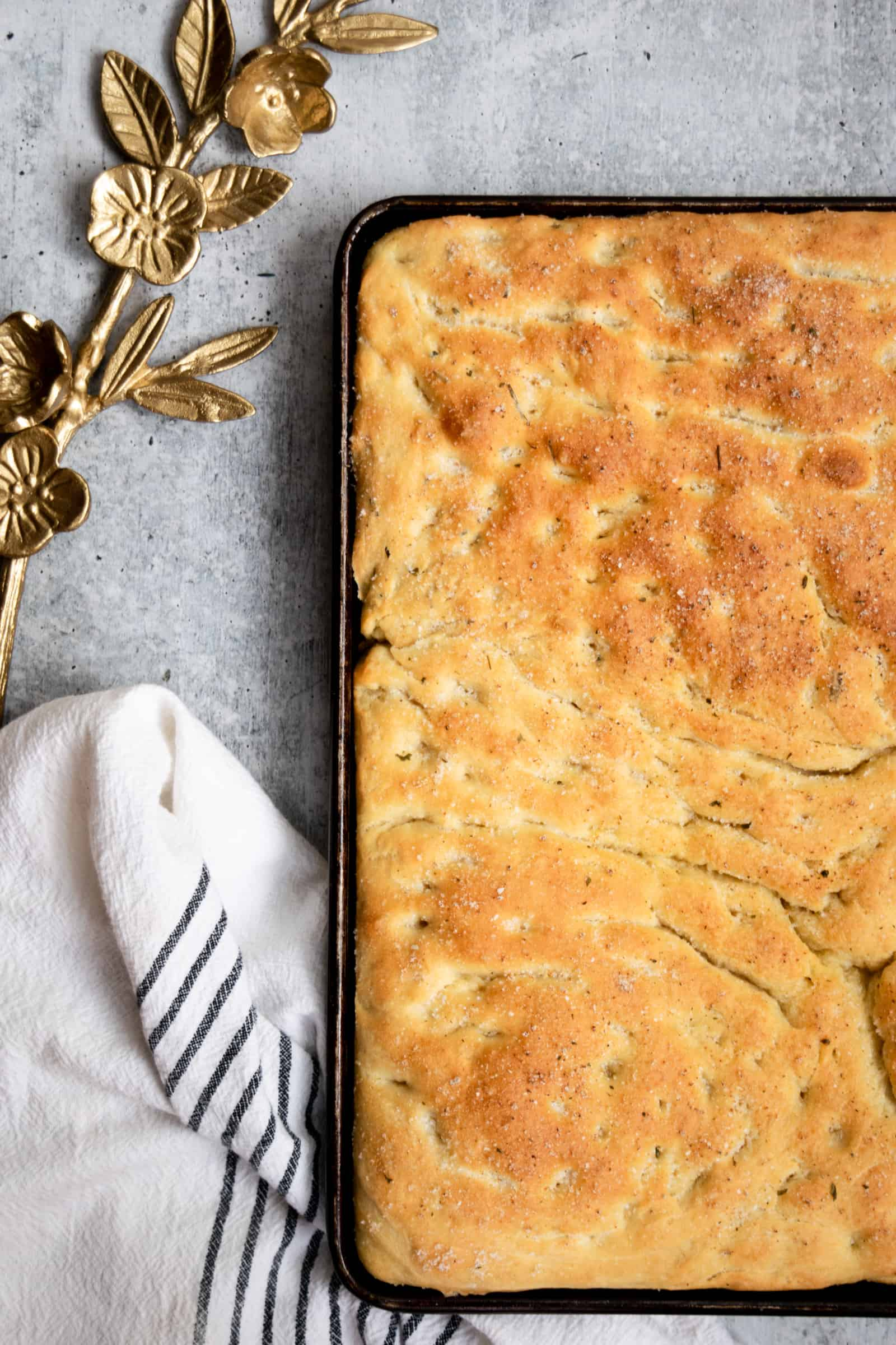 baked focaccia in a sheet pan resting on a black and white striped towel with gold vine accessory