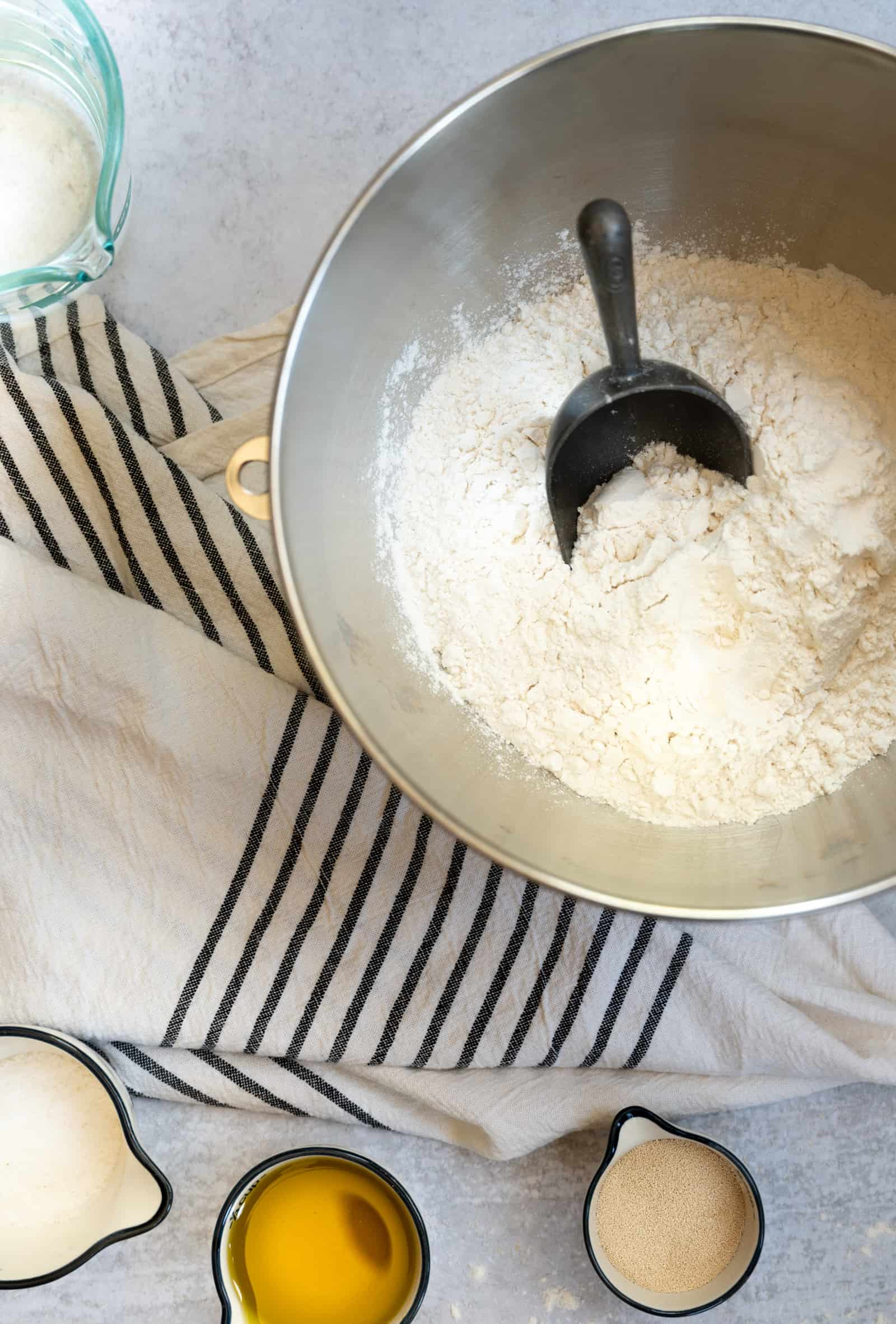 stainless bowl of flour with a metal scoop on a black and white striped dish towel with bowls of oil, yeast and salt