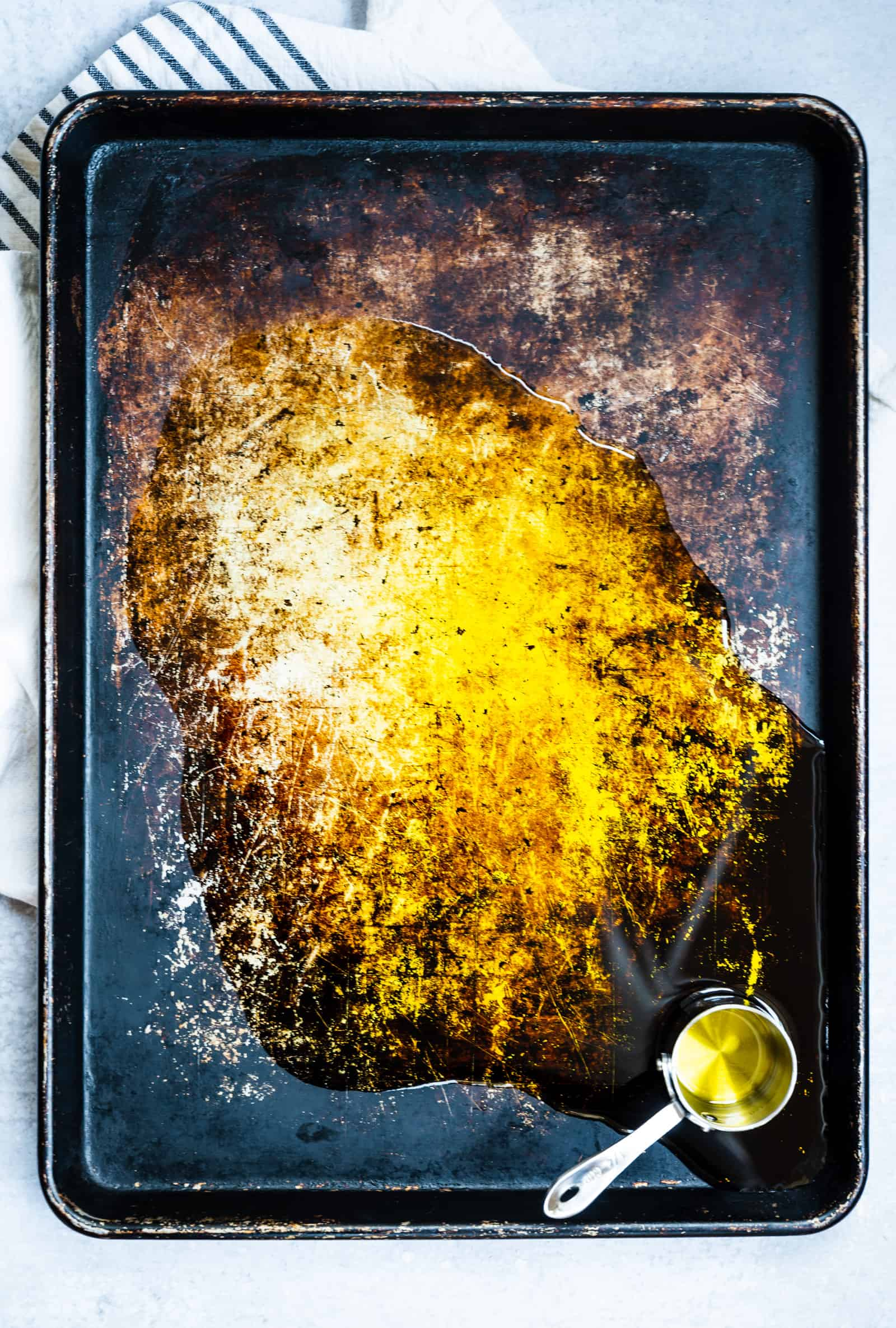 worn sheet pan with olive oil spilled on it and a stainless measuring cup