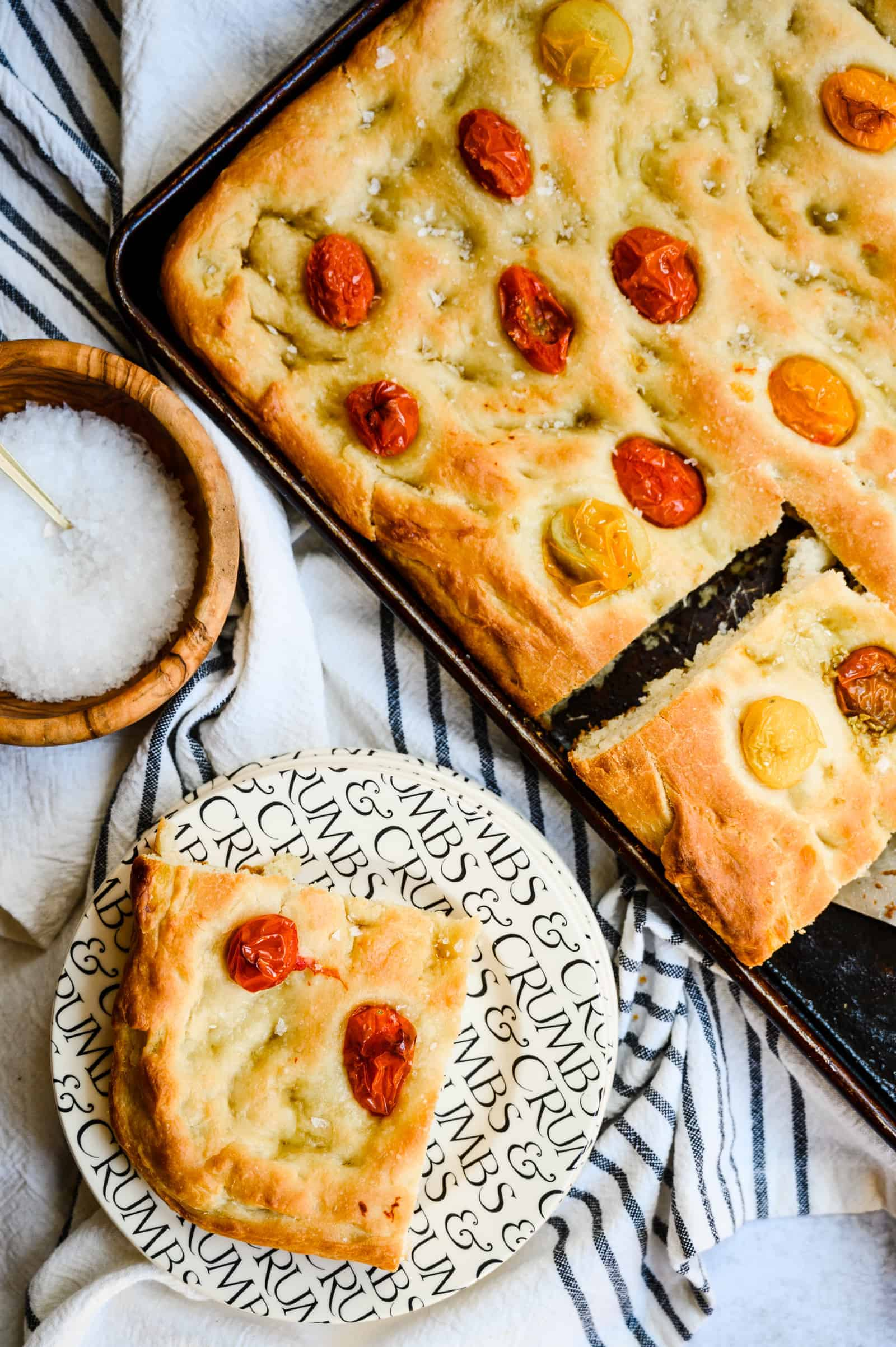 sheet pan of baked focaccia with tomatoes in it and a bowl of salt and piece of focaccia on a black and white plate