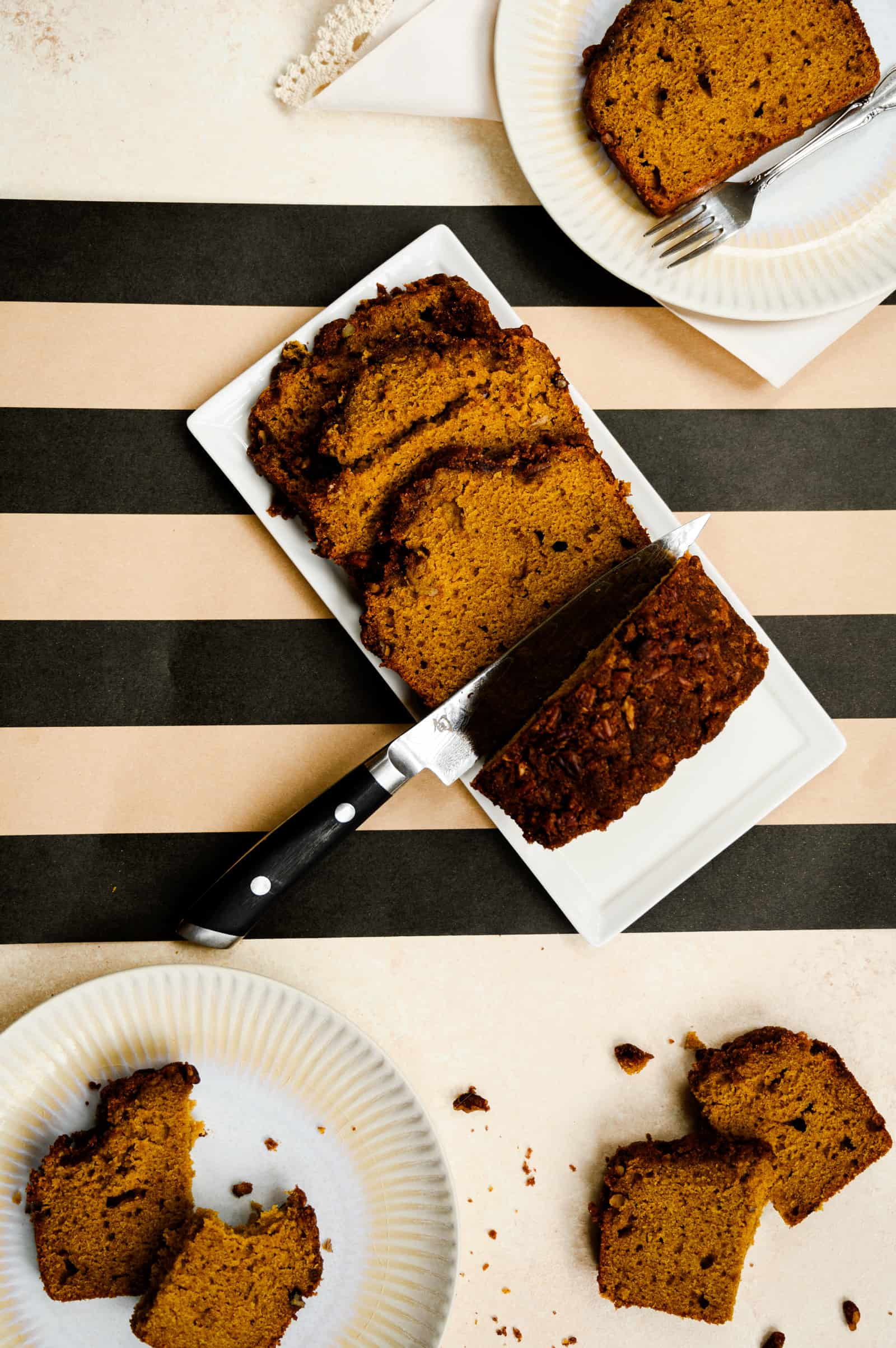 overhead of loaf of cut pumpkin bread on a white plate and a black and tan striped background