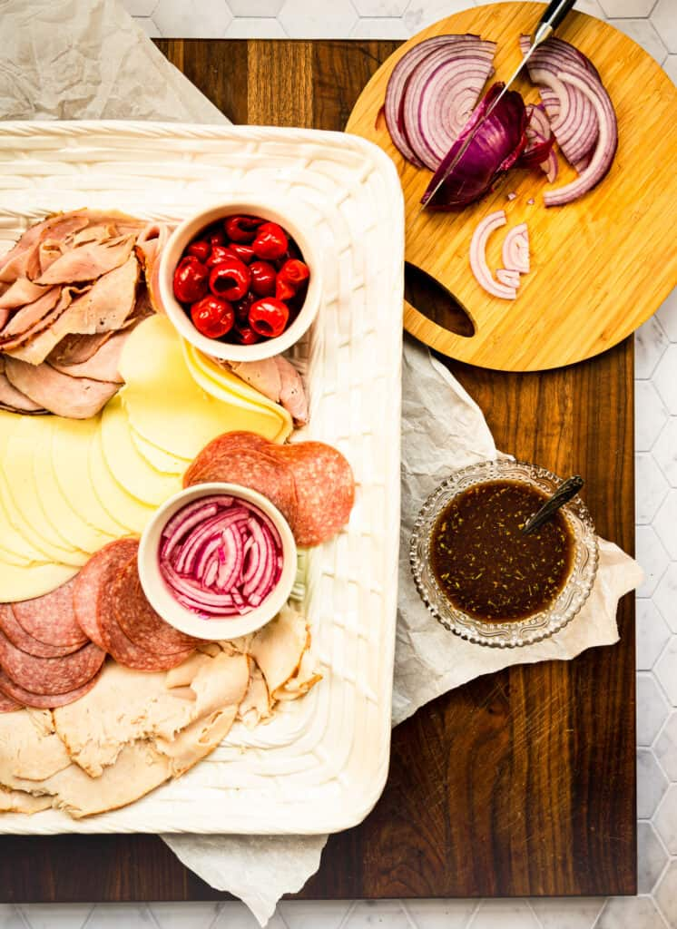 a white basket tray of cold cuts and bowls of red onions and peppadew pepper