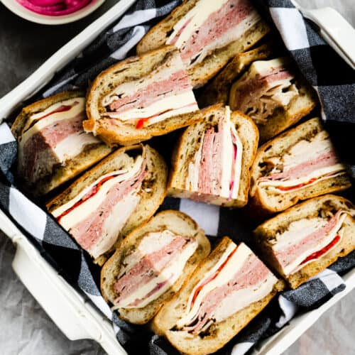 a white ceramic basket with black and white gingham napkin in it filled with pressed meat and cheese sandwiches