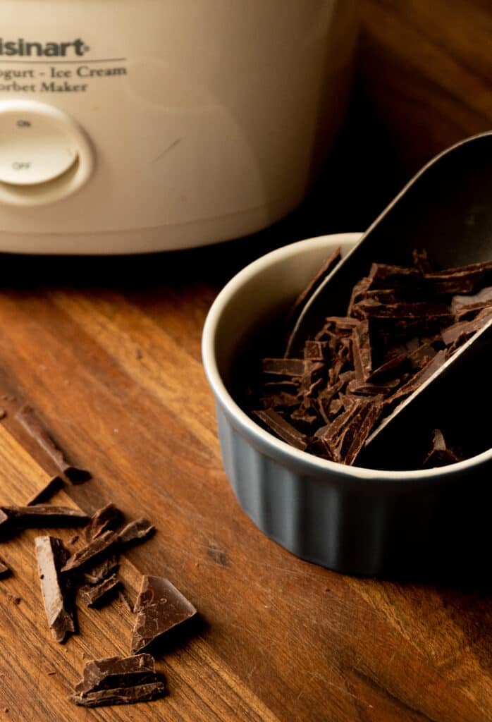 blue bowl with dark chocolate shavings and a scoop with an ice cream maker