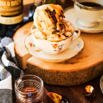 ice cream in a tea cup with hot espresso spilling over and a shot glass of whiskey and copper spoons.