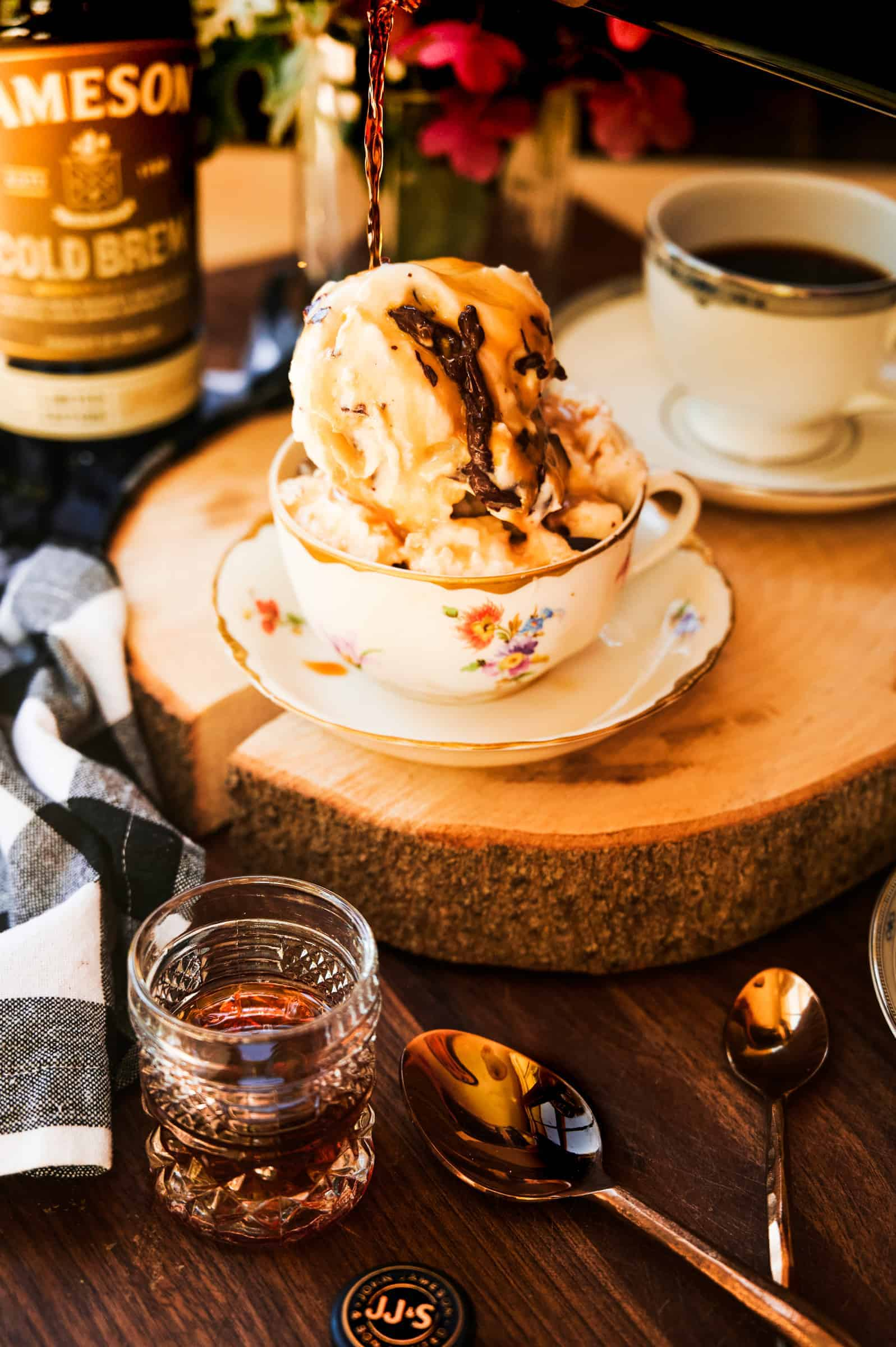 ice cream in a tea cup with hot espresso spilling over and a shot glass of whiskey and copper spoons