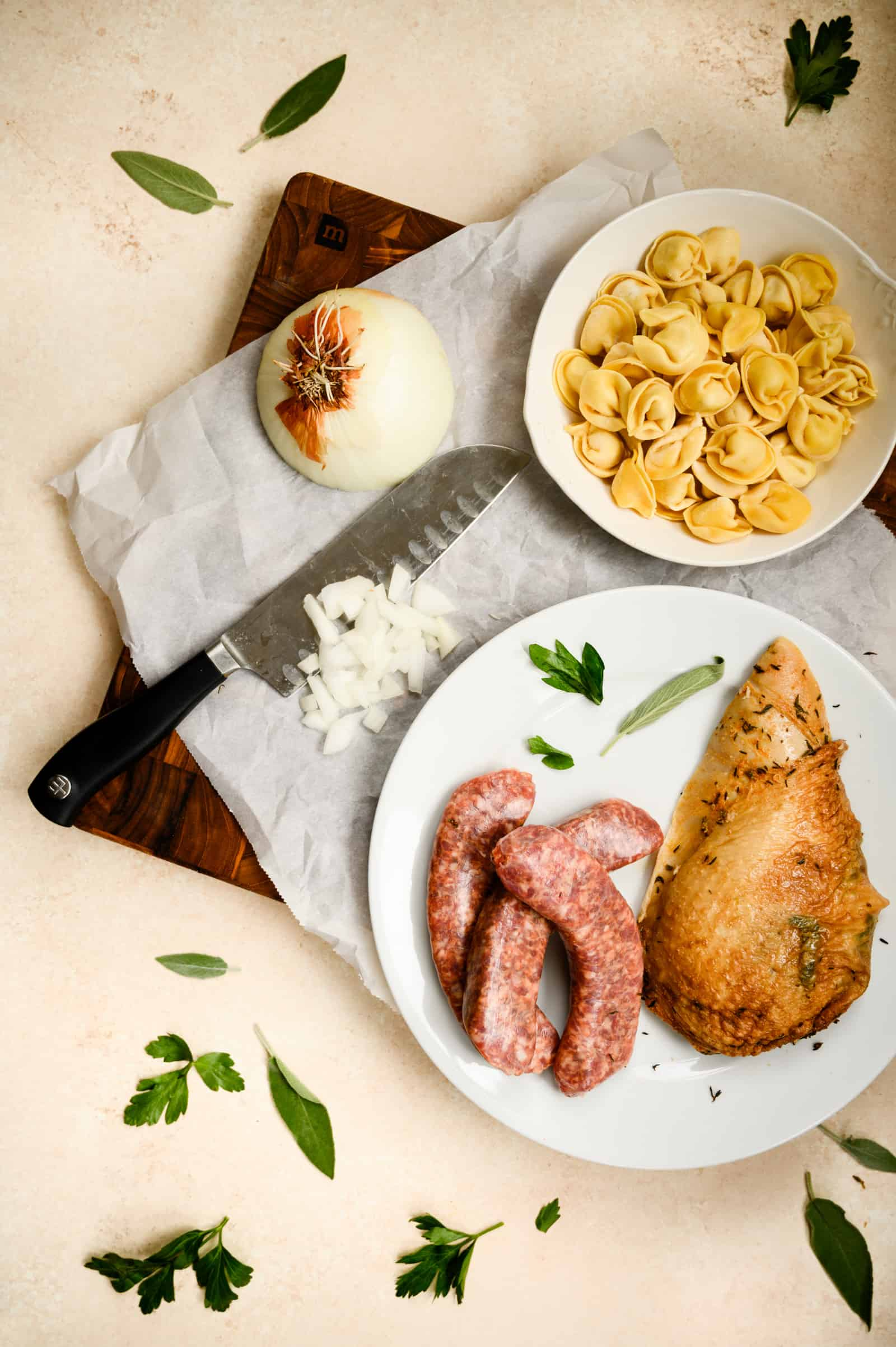 cutting board with knife, a chopped onion, white bowl of raw tortellini and white plate of turkey breast and Italian sausage