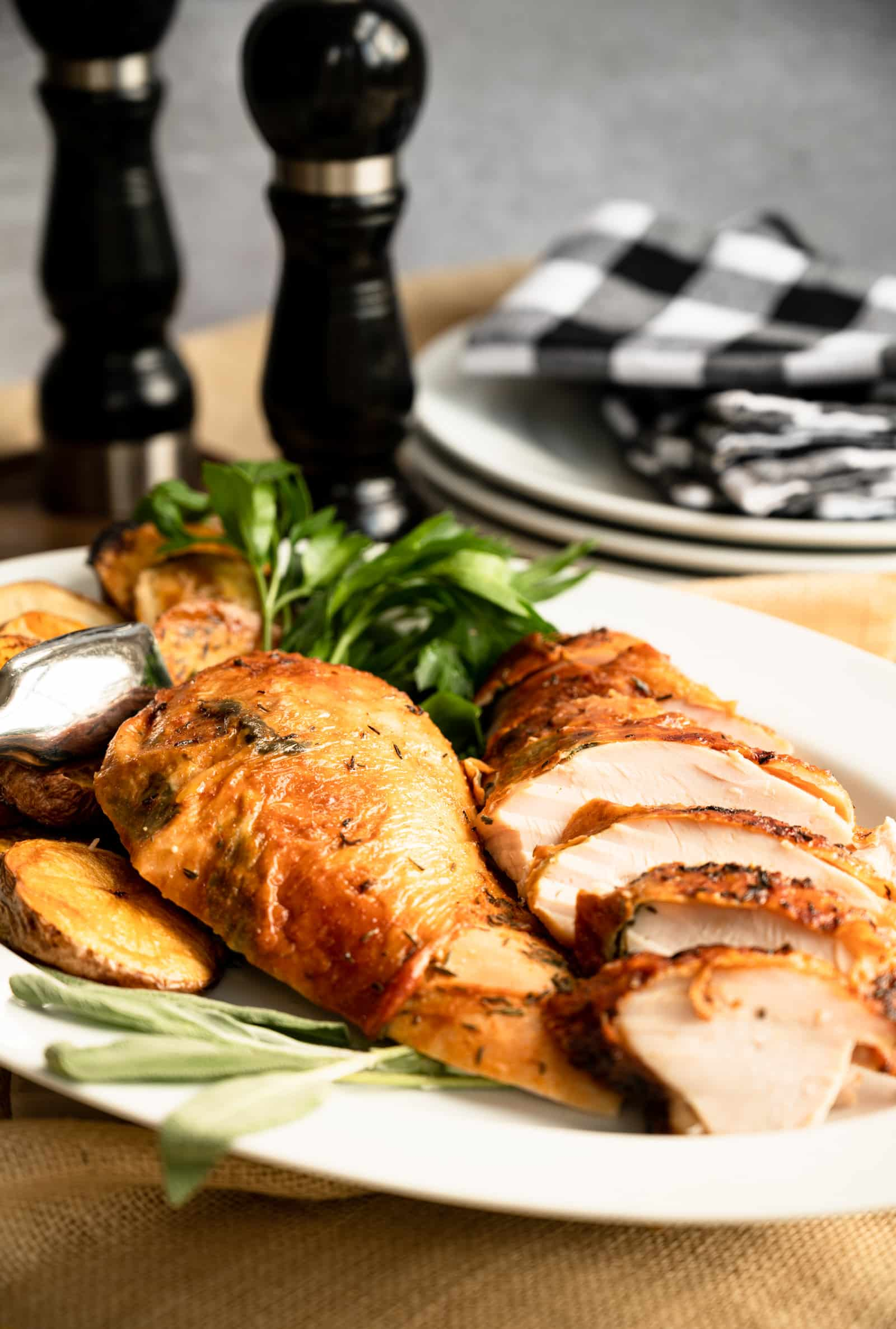 white platter of sliced roast turkey breast with the skin on it and some sage and parsley