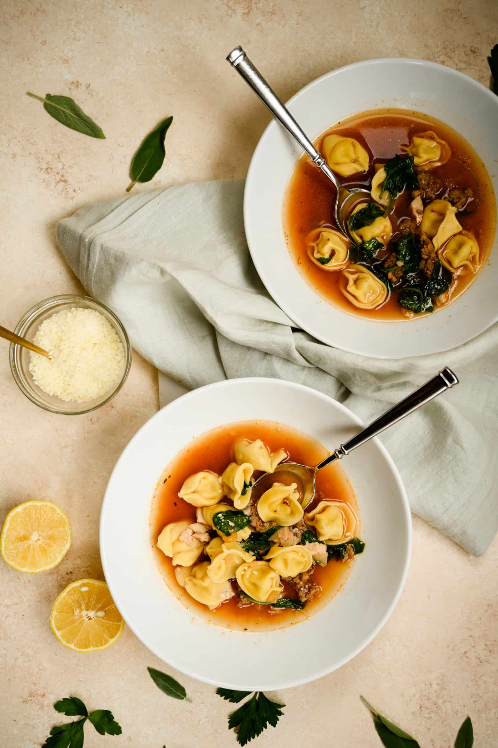 two bowls of tortellini soup with cut lemons and bowl of grated parmesan