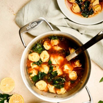 stockpot of tortellini soup with two white serving bowls of soup with spoons in them