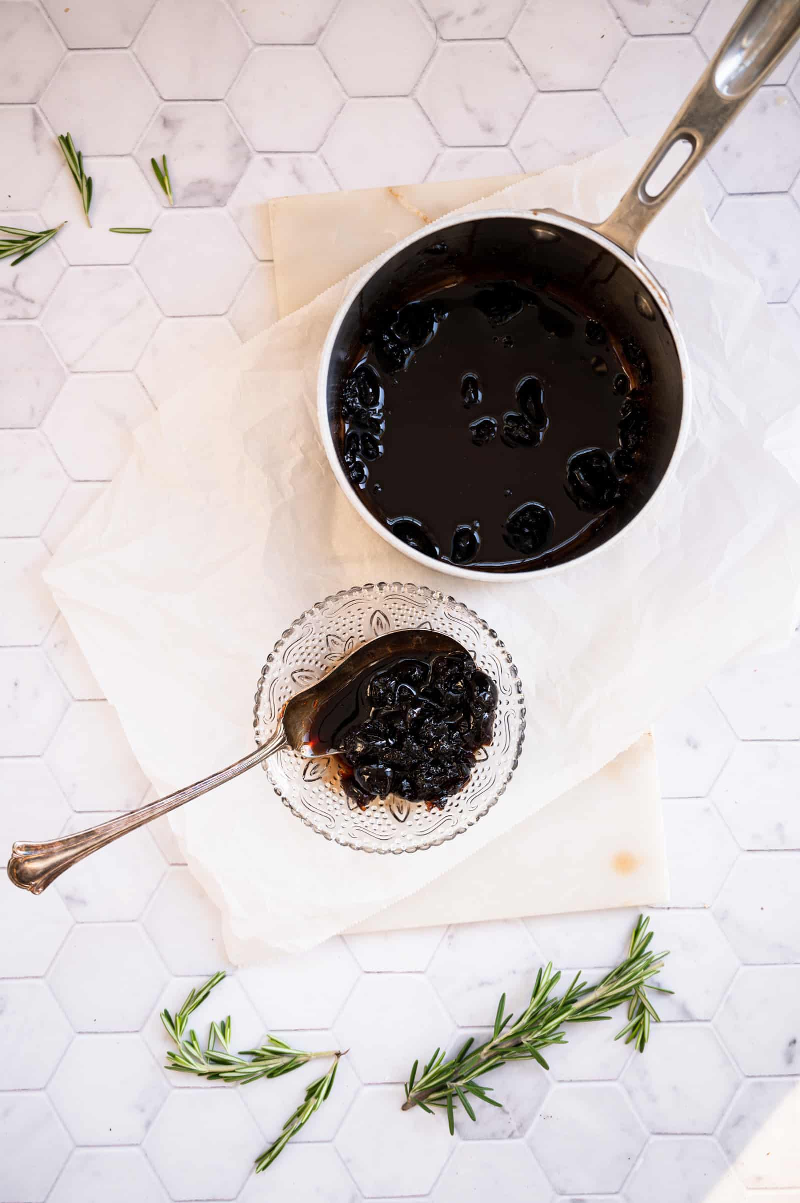saucepan and glass dish of cherry compote with sprigs of fresh rosemary