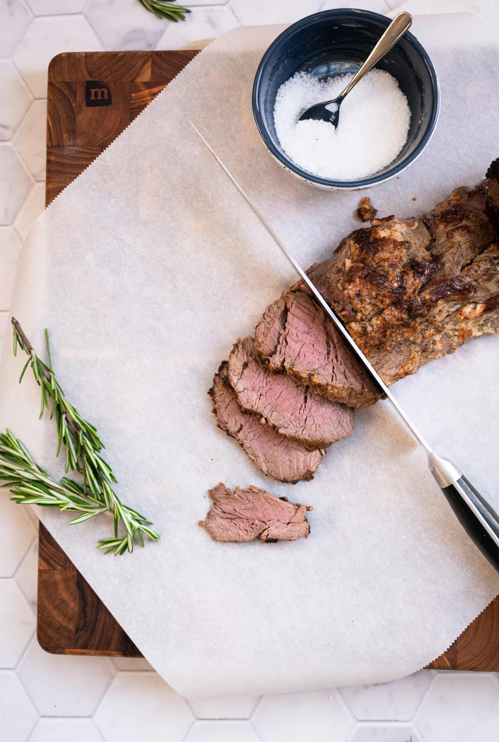 cutting board of beef tenderloin being sliced with sprig of fresh rosemary and bowl of kosher salt