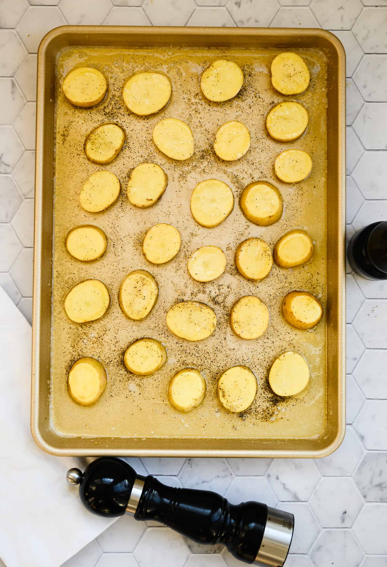 sheet pan of melted butter with sliced Yukon Gold potatoes