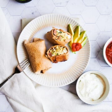 plate of 2 breakfast burritos cut with half of an avocado and bowls of salsa and sour cream