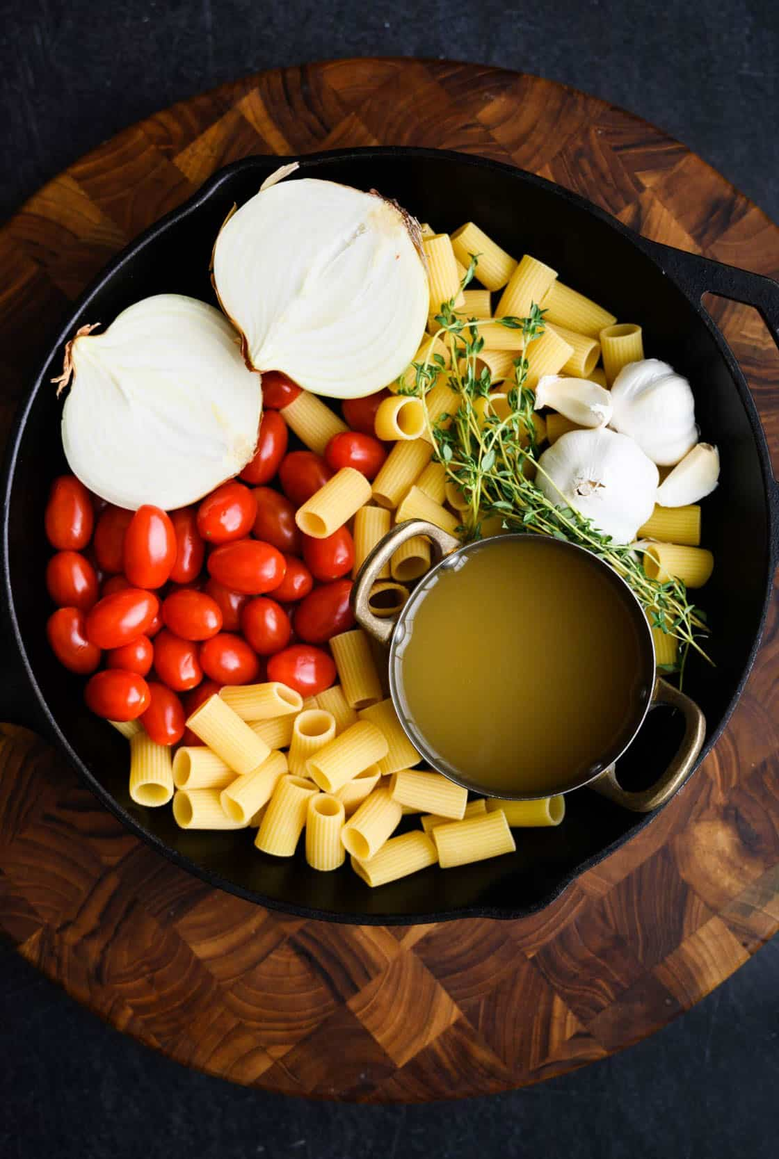 cast iron skillet filled with raw rigatoni, white onion, heads of garlic, fresh thyme and grape tomatoes and a small skillet of broth