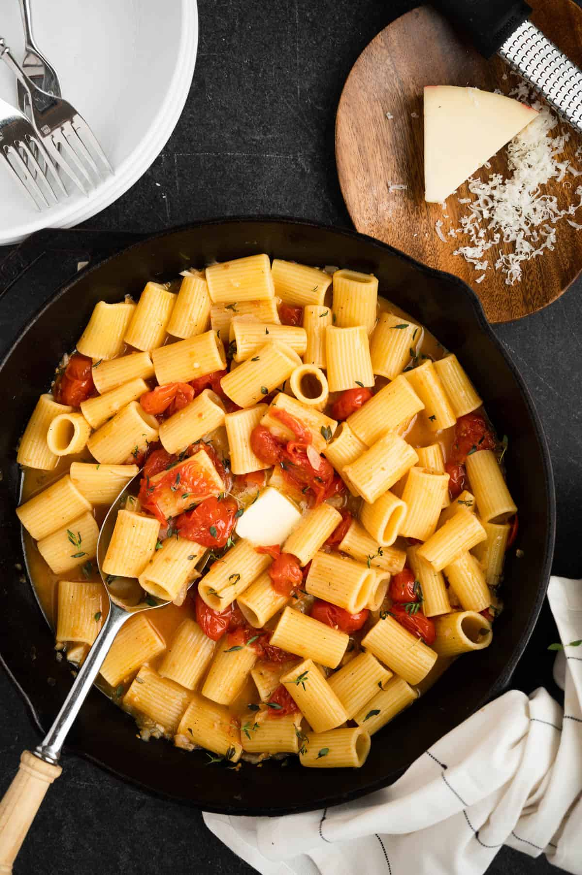 pat of butter on pan of rigatoni and tomatoes in a cast iron skillet