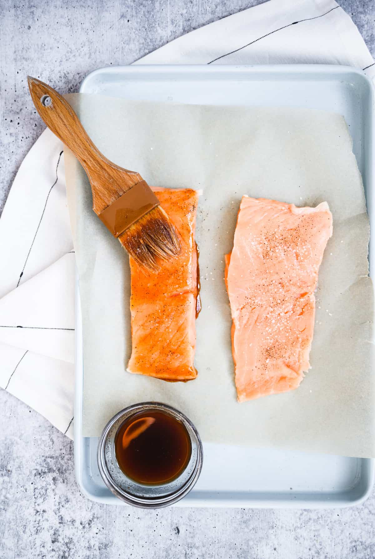 two pieces of raw salmon with one being brushed with sauce