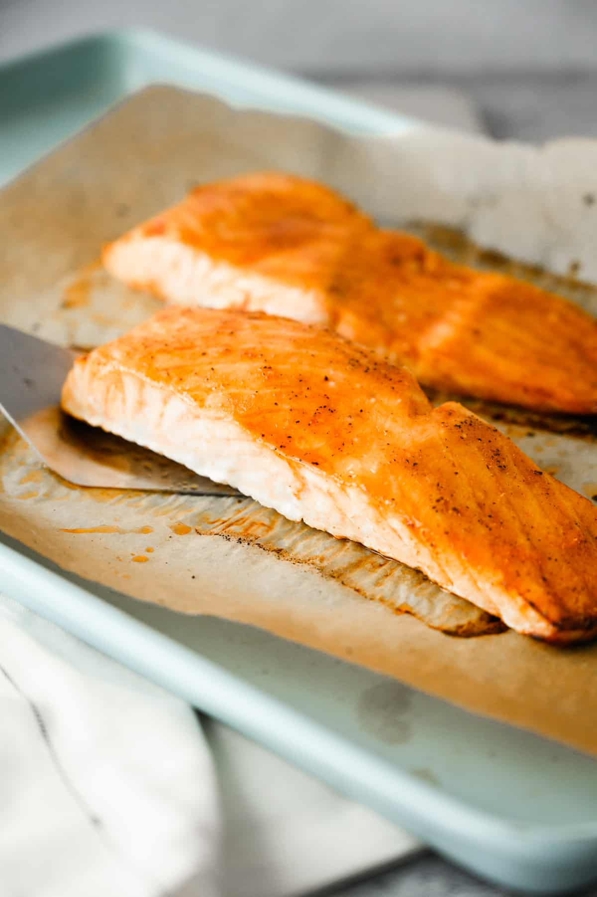 two pieces of roasted salmon on parchment covered baking sheet with a spatula