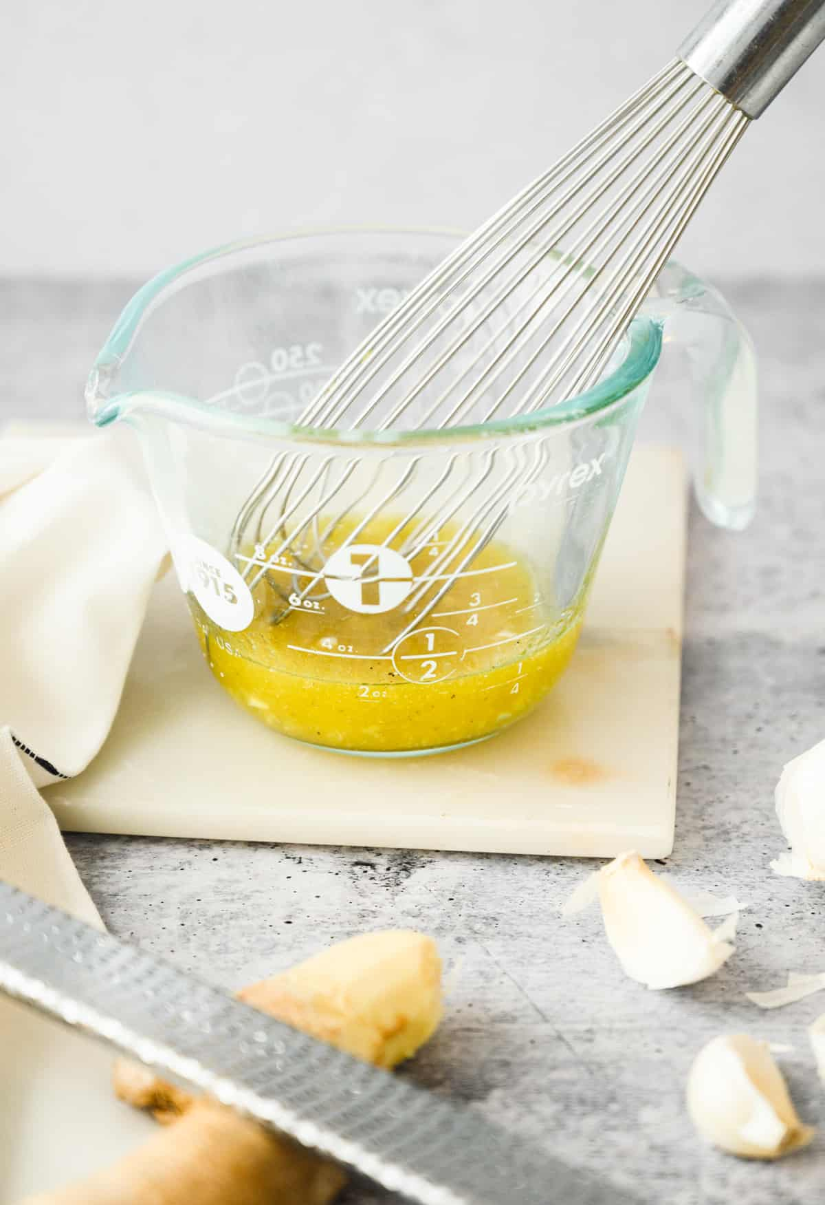 whisk in glass measuring cup with salad dressing in it