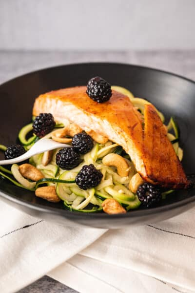black bowl with zucchini noodles and a piece of roasted salmon on top with blackberries.