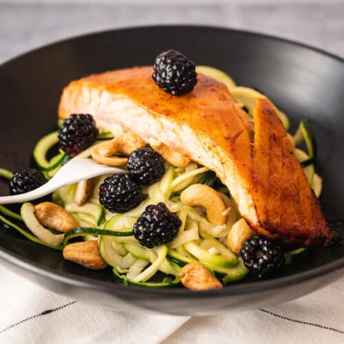black bowl with zucchini noodles and a piece of roasted salmon on top with blackberries