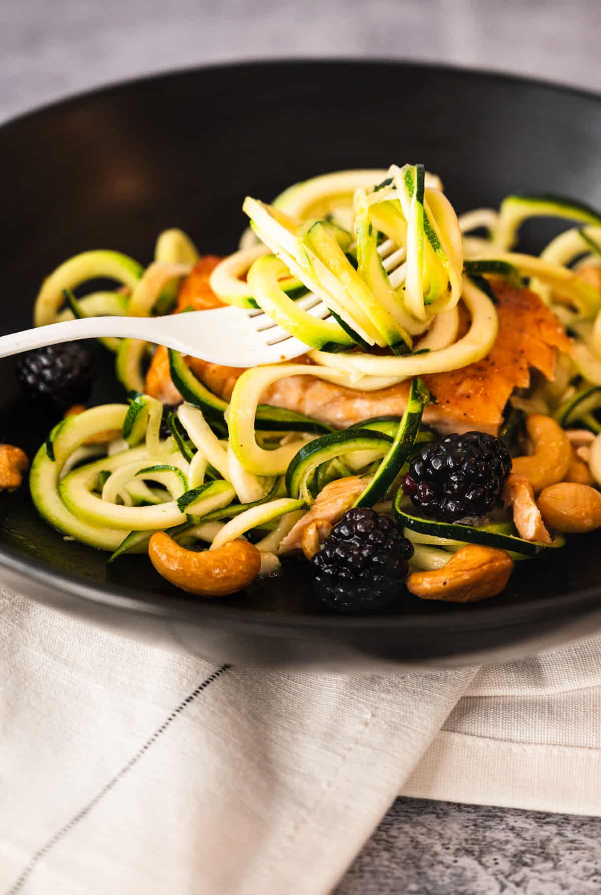 close up of a white fork twirling zucchini noodles with salmon and blackberries