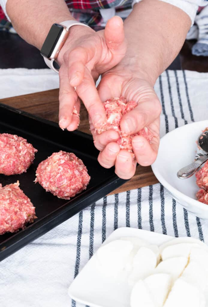 hand making meatballs with a tray of meatballs and bowl of fresh mozzarella