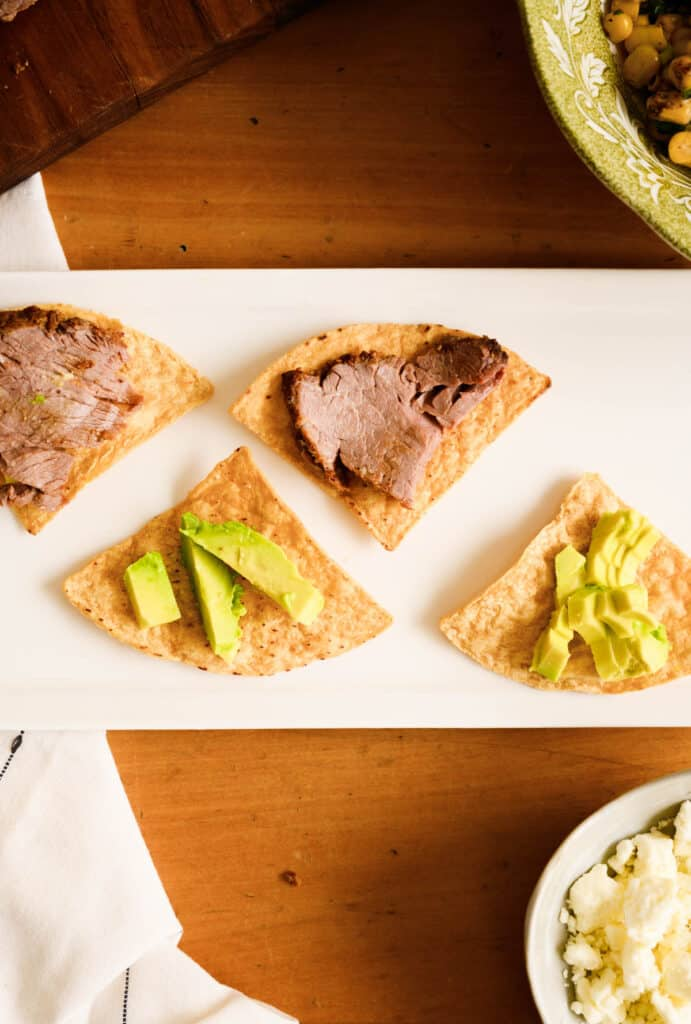 white tray with two tortilla chips and beef and two with sliced avocado