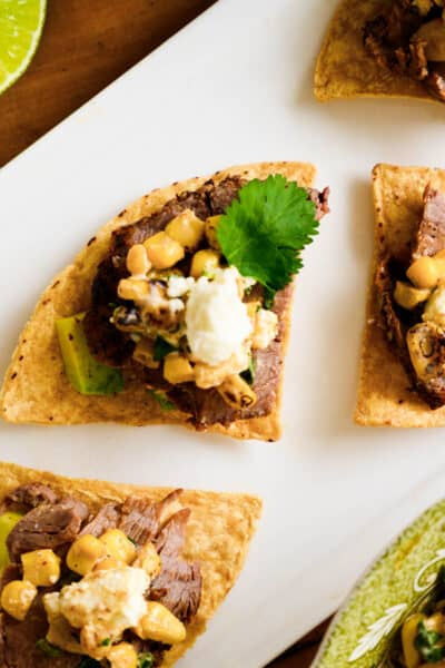 zoom of a beef and street corn nacho with cotija cheese and cilantro leaf.