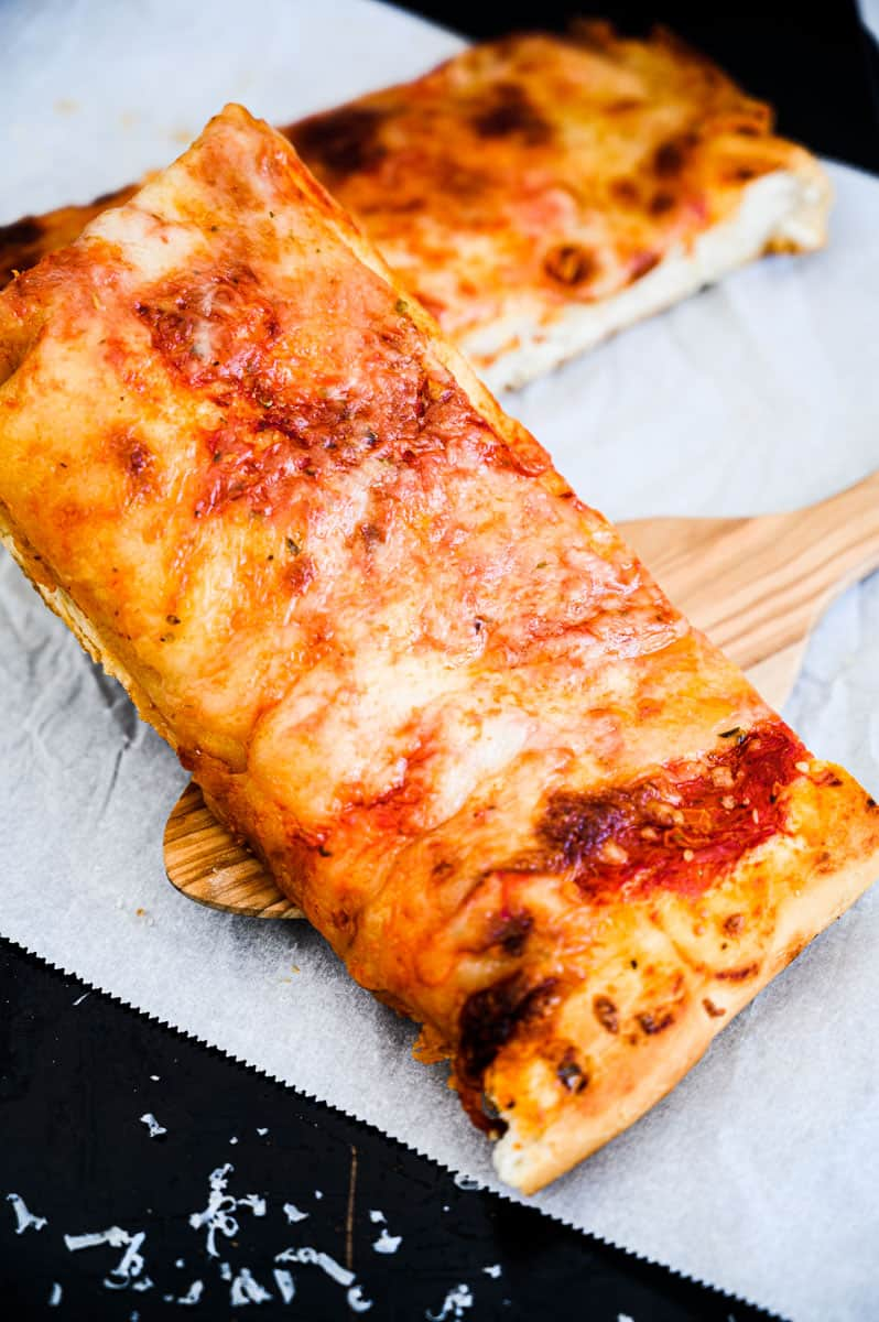 two slices of pizza being served by a wooden spatula on parchment with a sprinkling of parmesan