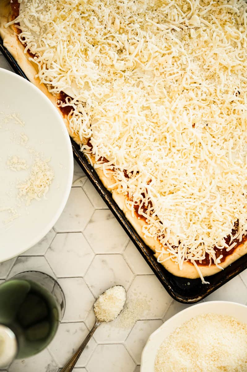 mozzarella cheese topped pizza in a sheet pan with bowls of cheese and bottle of olive oil
