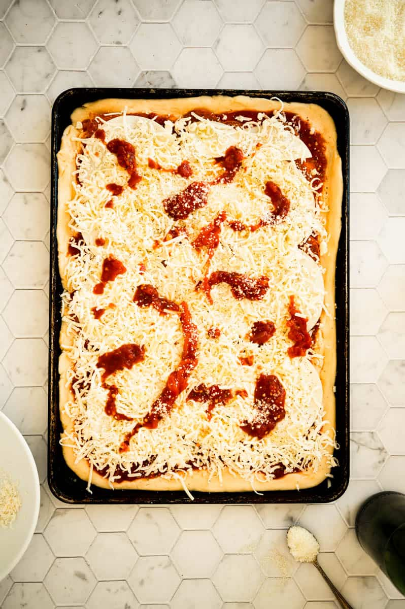 overhead of uncooked homemade pizza topped with cheese and sauce