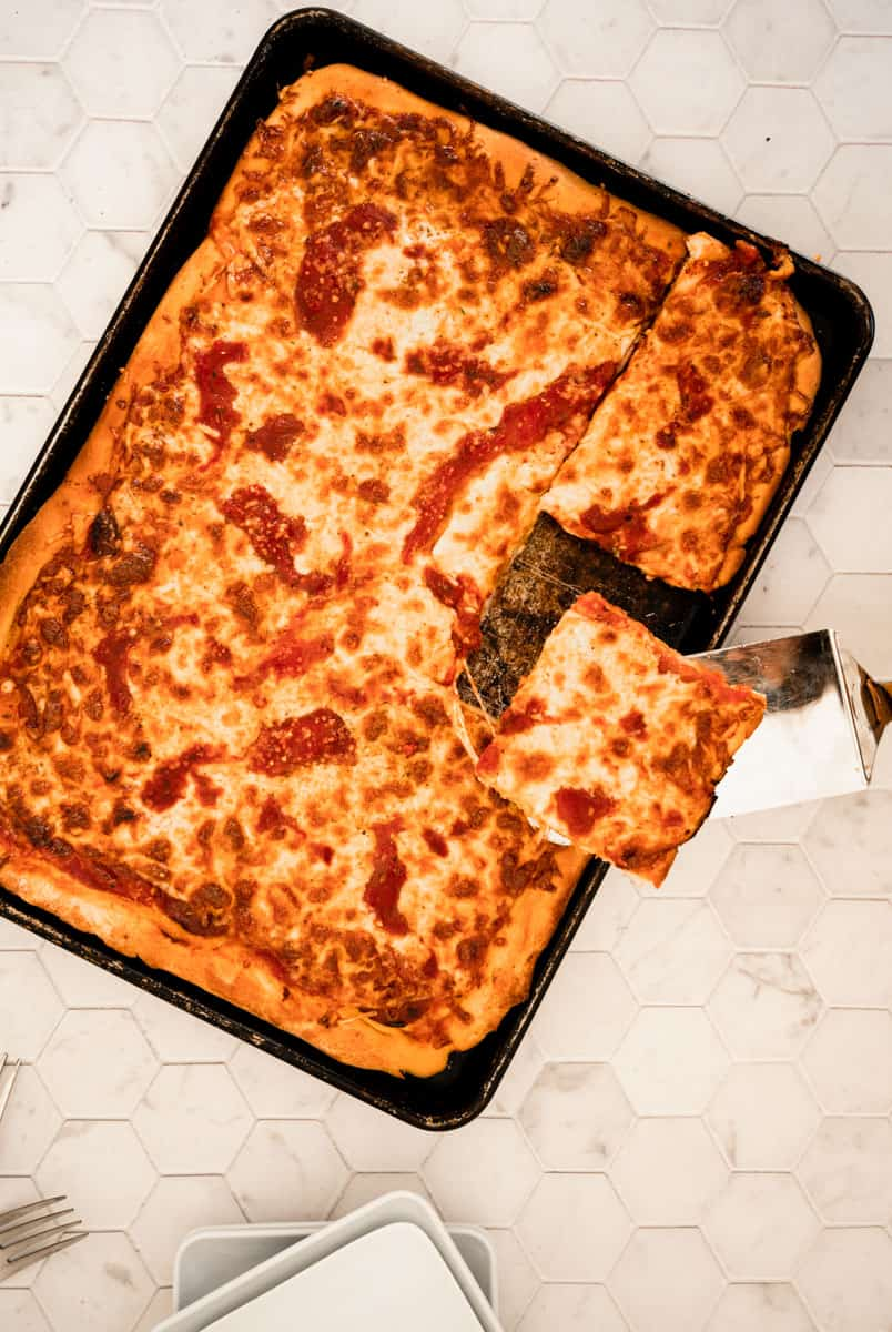 baked pizza in a sheet pan with spatula removing a piece.