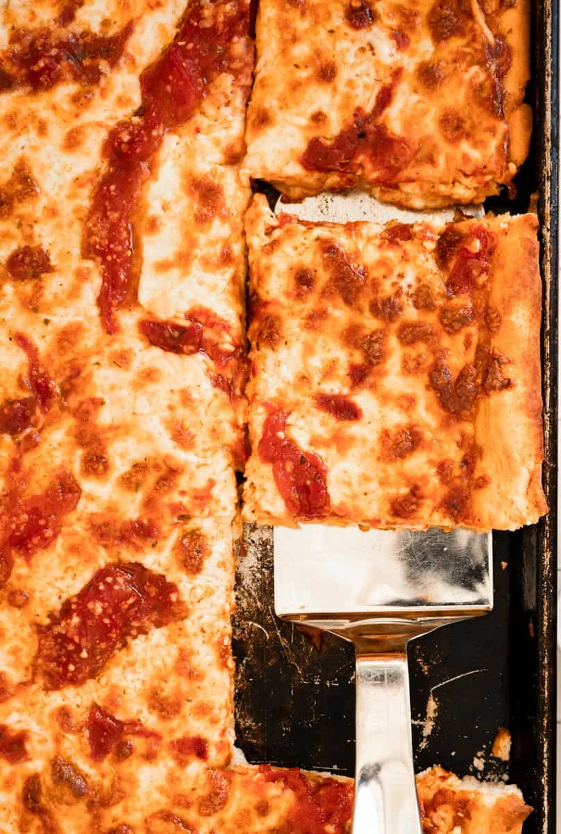 close up of homemade pizza slice being removed from a sheet pan