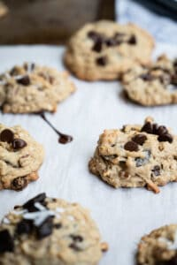 a parchment covered table of oatmeal and chocolate chip cookies with a chocolate smear.