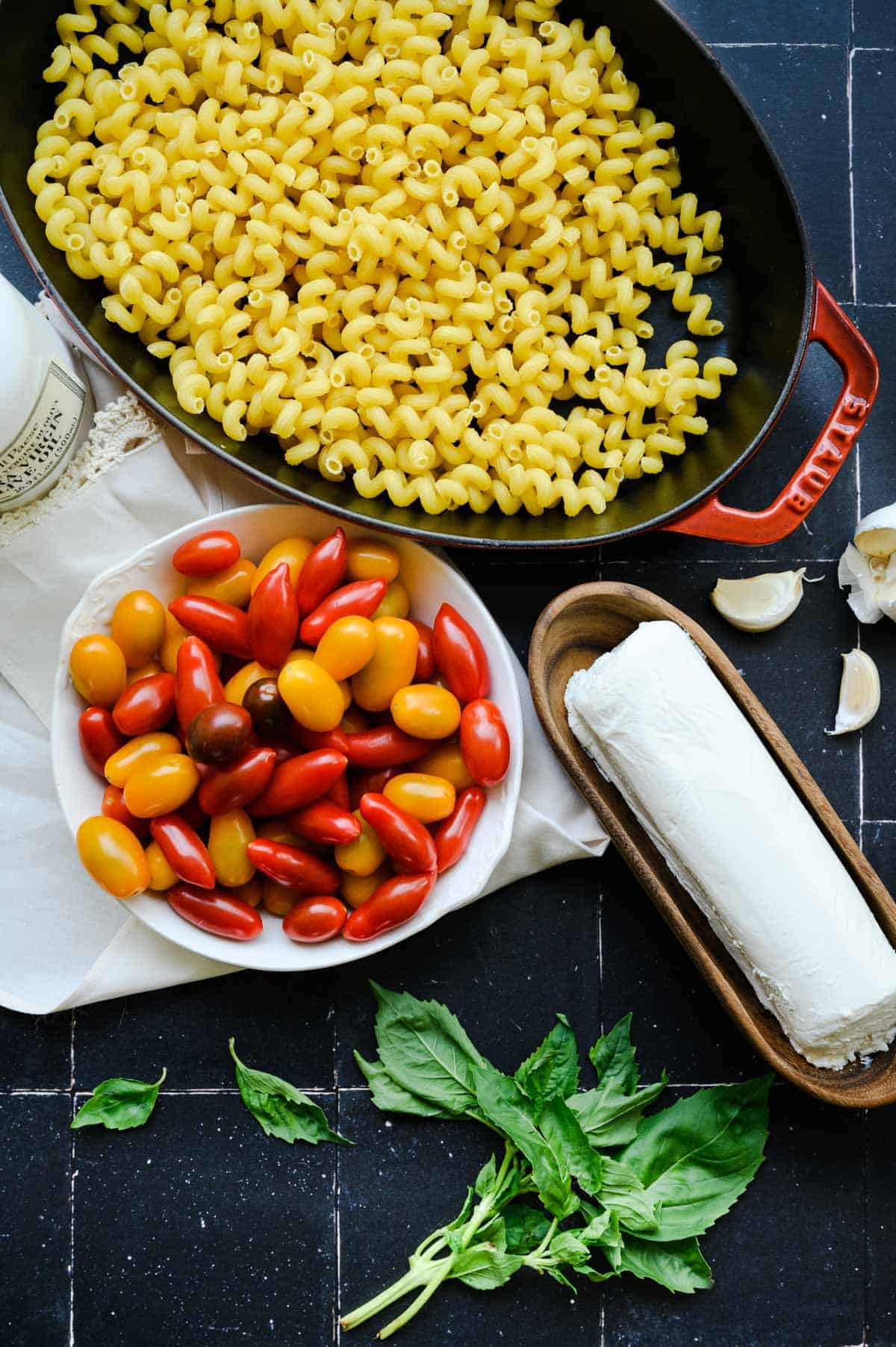 white bowl with grape tomatoes, wooden tray of goat cheese and a baking pan of cavatappi pasta