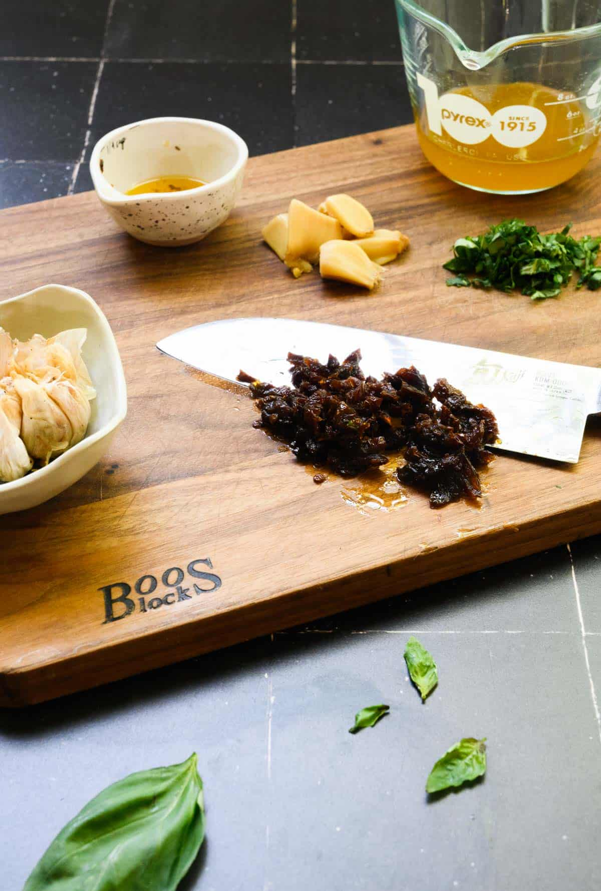wooden board with knife chopping sun dried tomatoes with garlic and basil