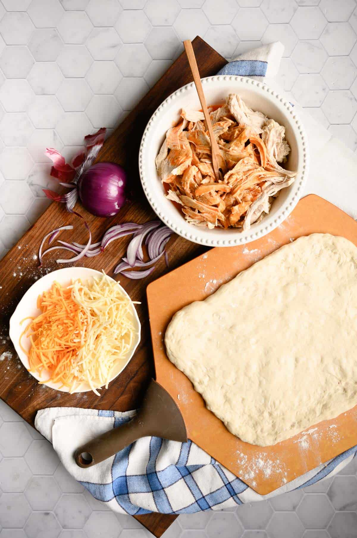 pizza peel with pizza dough rolled out and bowls of shredded chicken and cheese