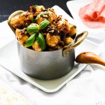 a galvanized bowl of marinated fresh mozzarella balls with basil.