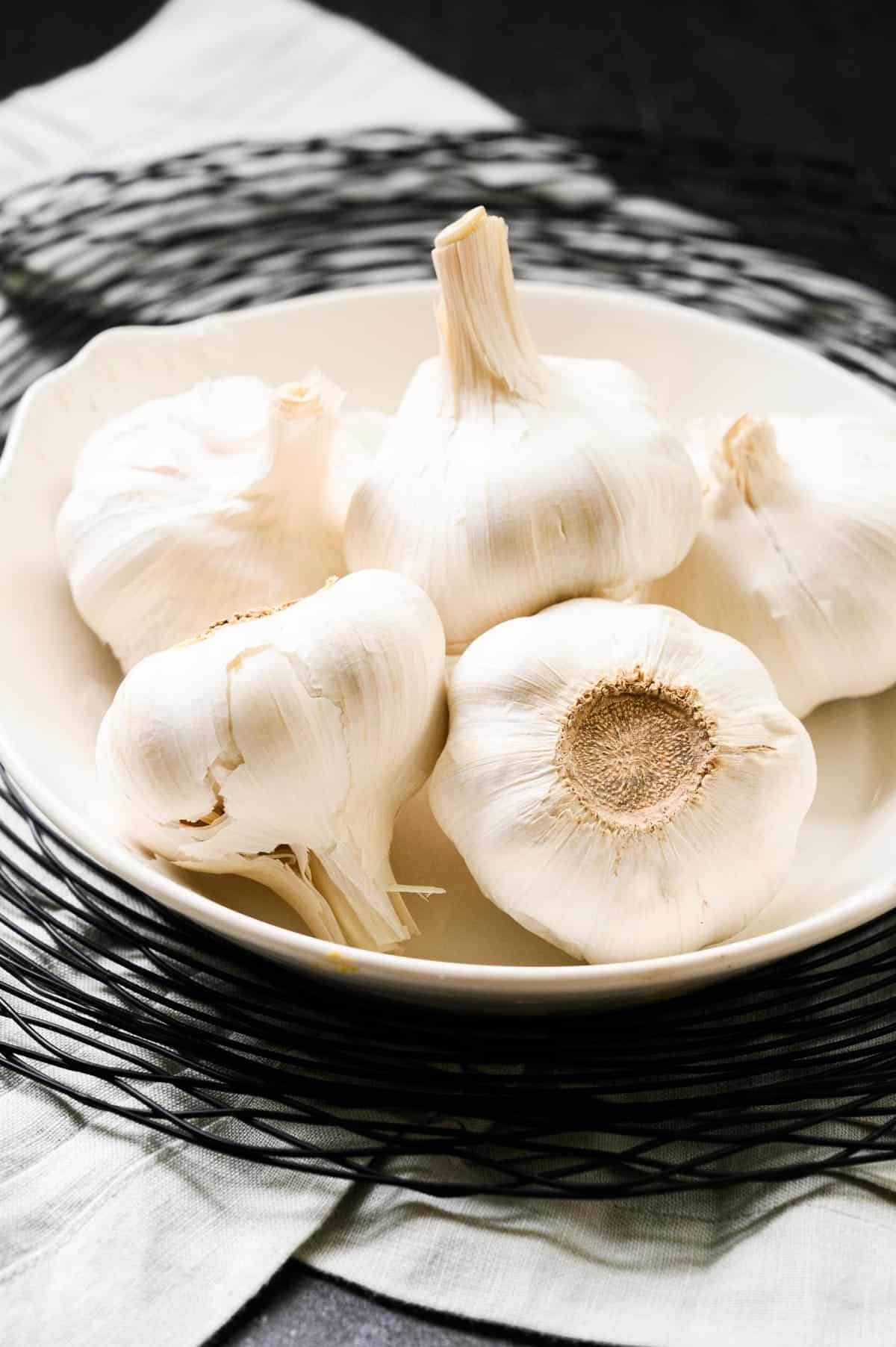 heads of garlic on a white plate with a black wire charger