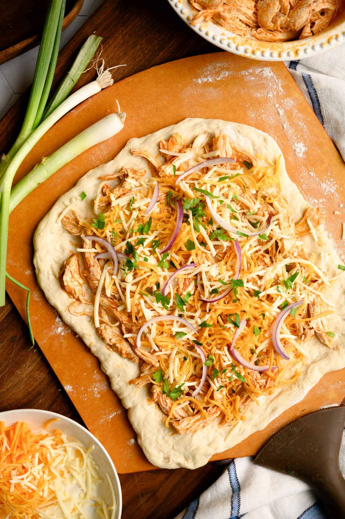 uncooked Buffalo chicken pizza with red onions and cilantro on top garnished with whole green onions