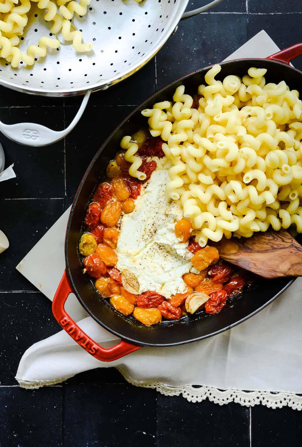 stirring cavatappi pasta into a pan of goat cheese tomato sauce