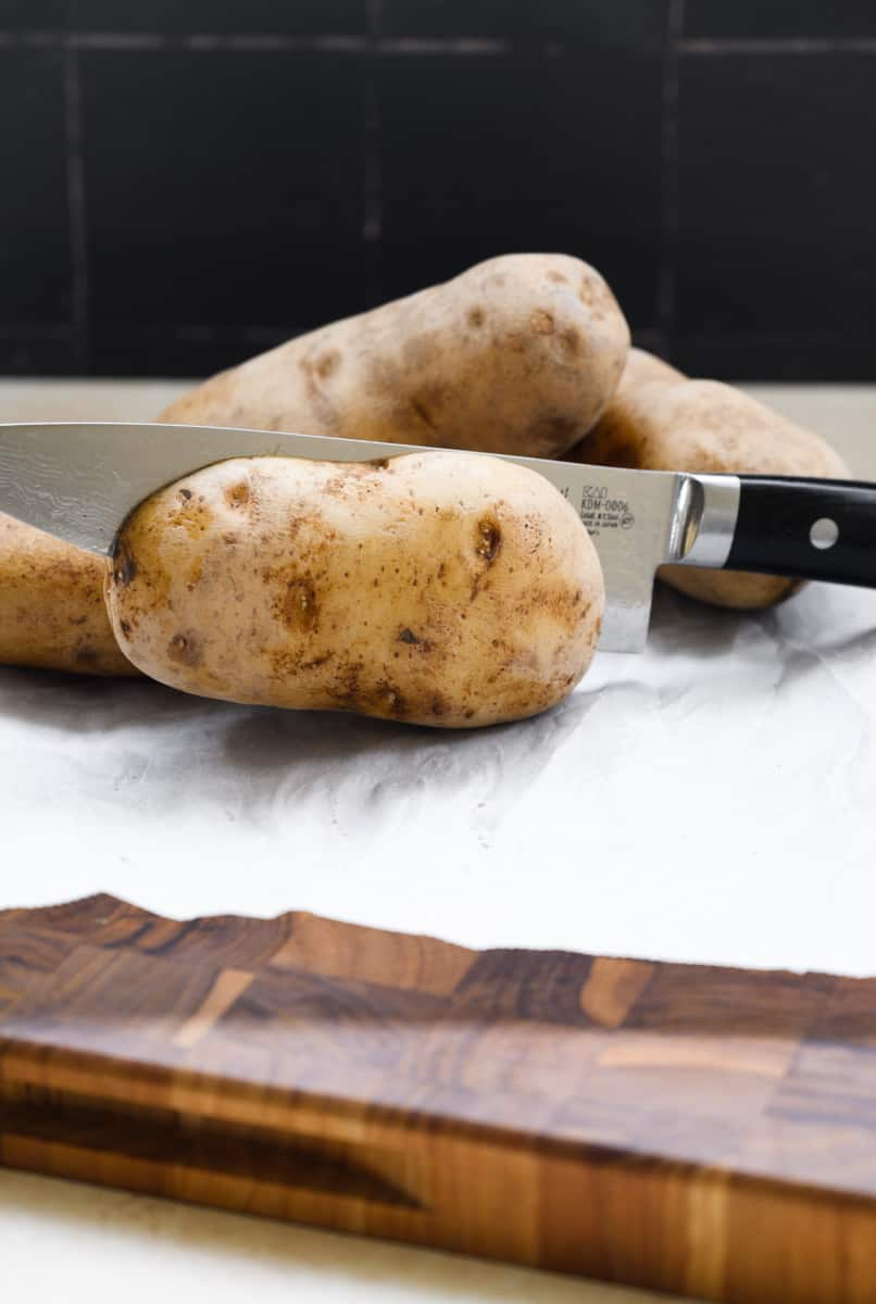 knife cutting through a potato on parchment covered cutting board