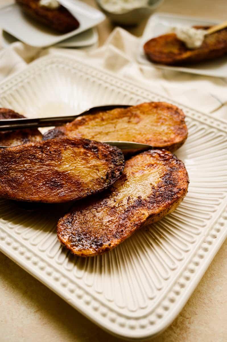 white ceramic platter of roasted potato halves