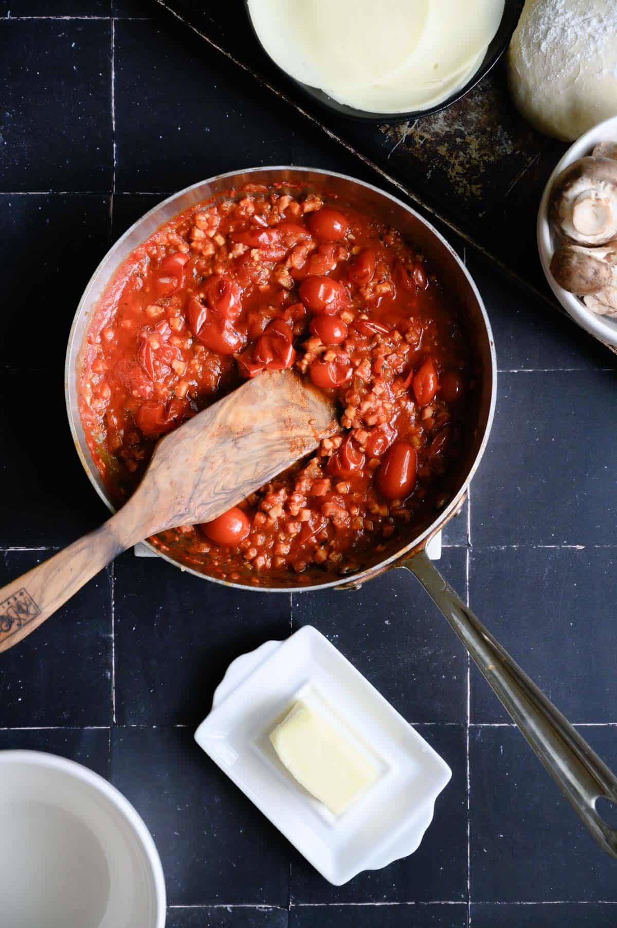 pizza sauce in a skillet with a wooden paddle