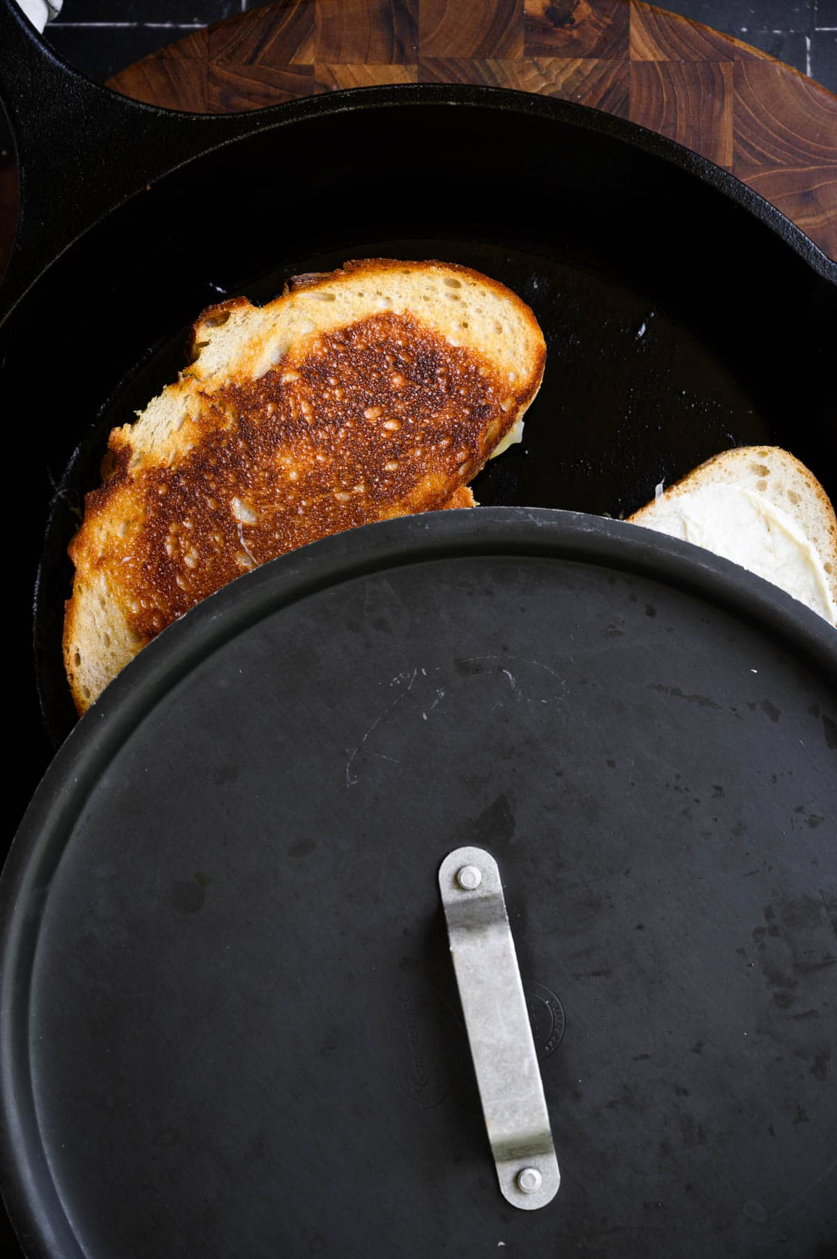 a cast iron skillet half covered by a black lid revealing half of a grilled sandwich.