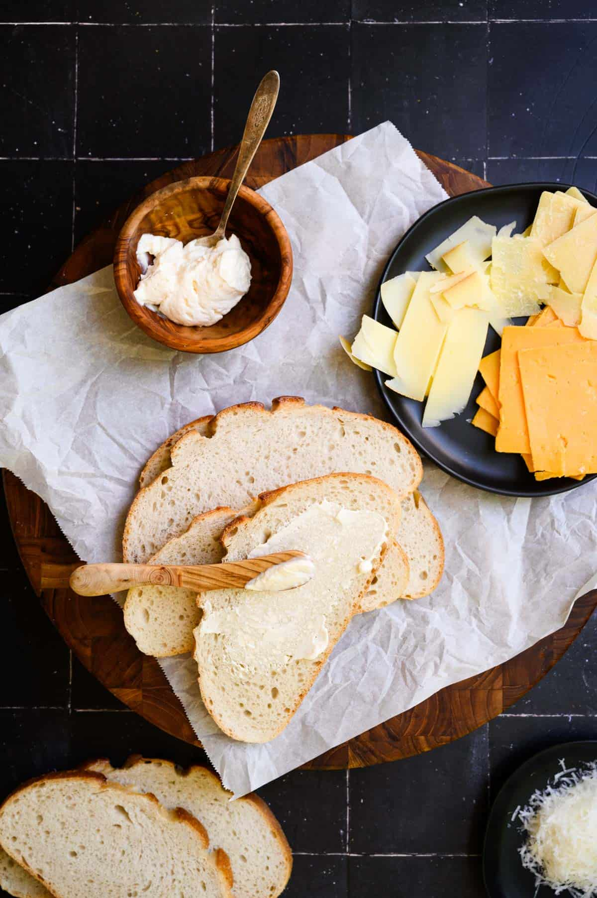 a black tiled background with mayo being spread on sliced bread and a plate of cheese slices.