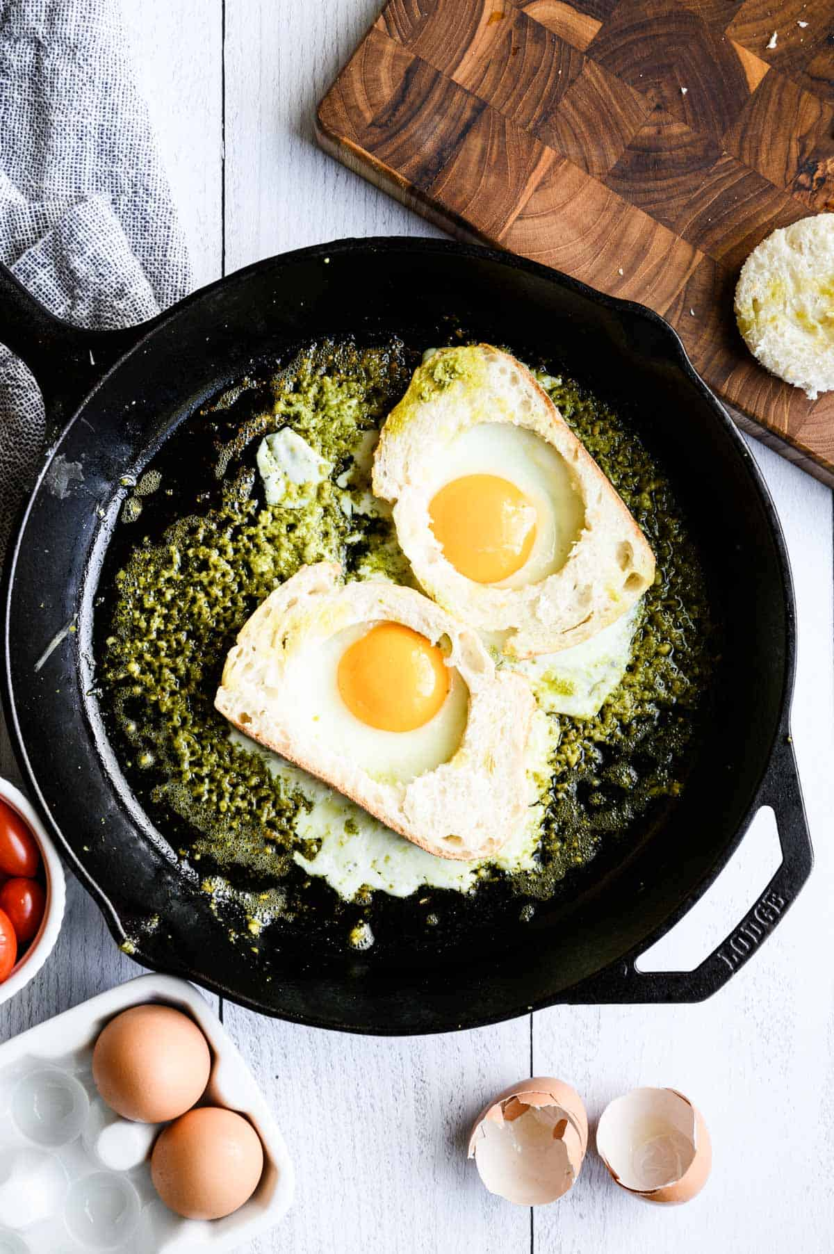 skillet with eggs in cut out bread cooking in pesto