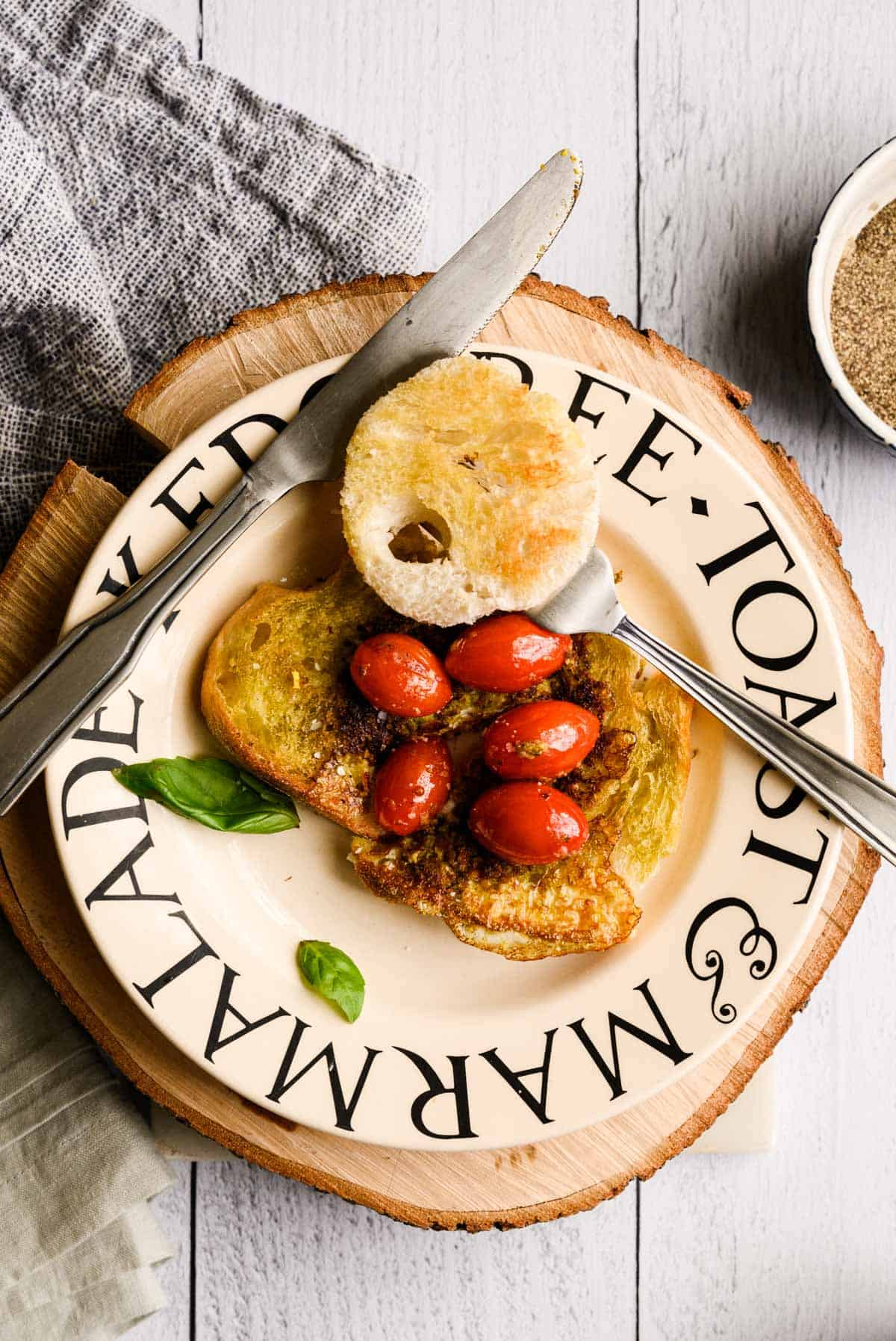 a piece of toasted bread with sauteed tomatoes and a circle of bread on top and basil on the plate