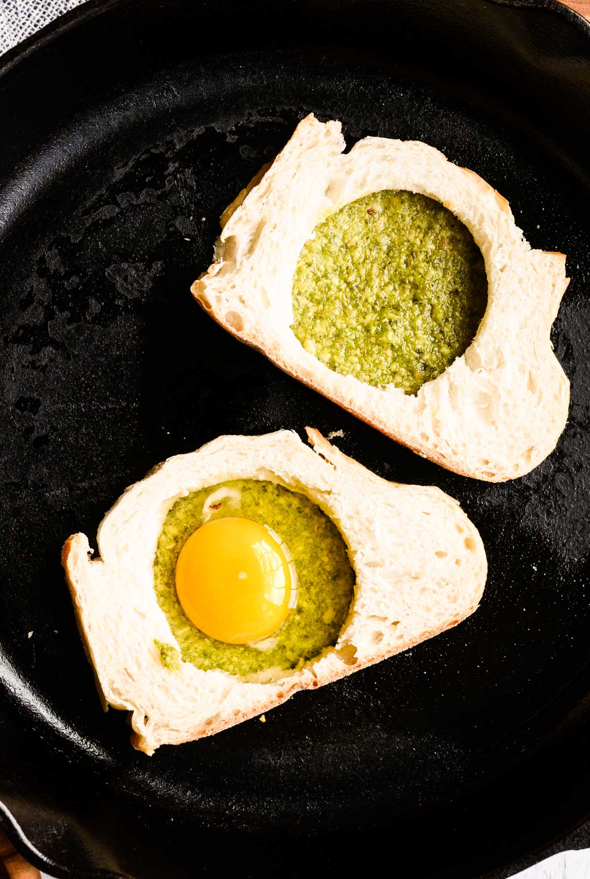 two pesto filled pieces of bread and one with an egg cooking in it